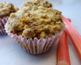 A photograph of some rhubarb and pumkin muffins with some rhubarb sticks on the side
